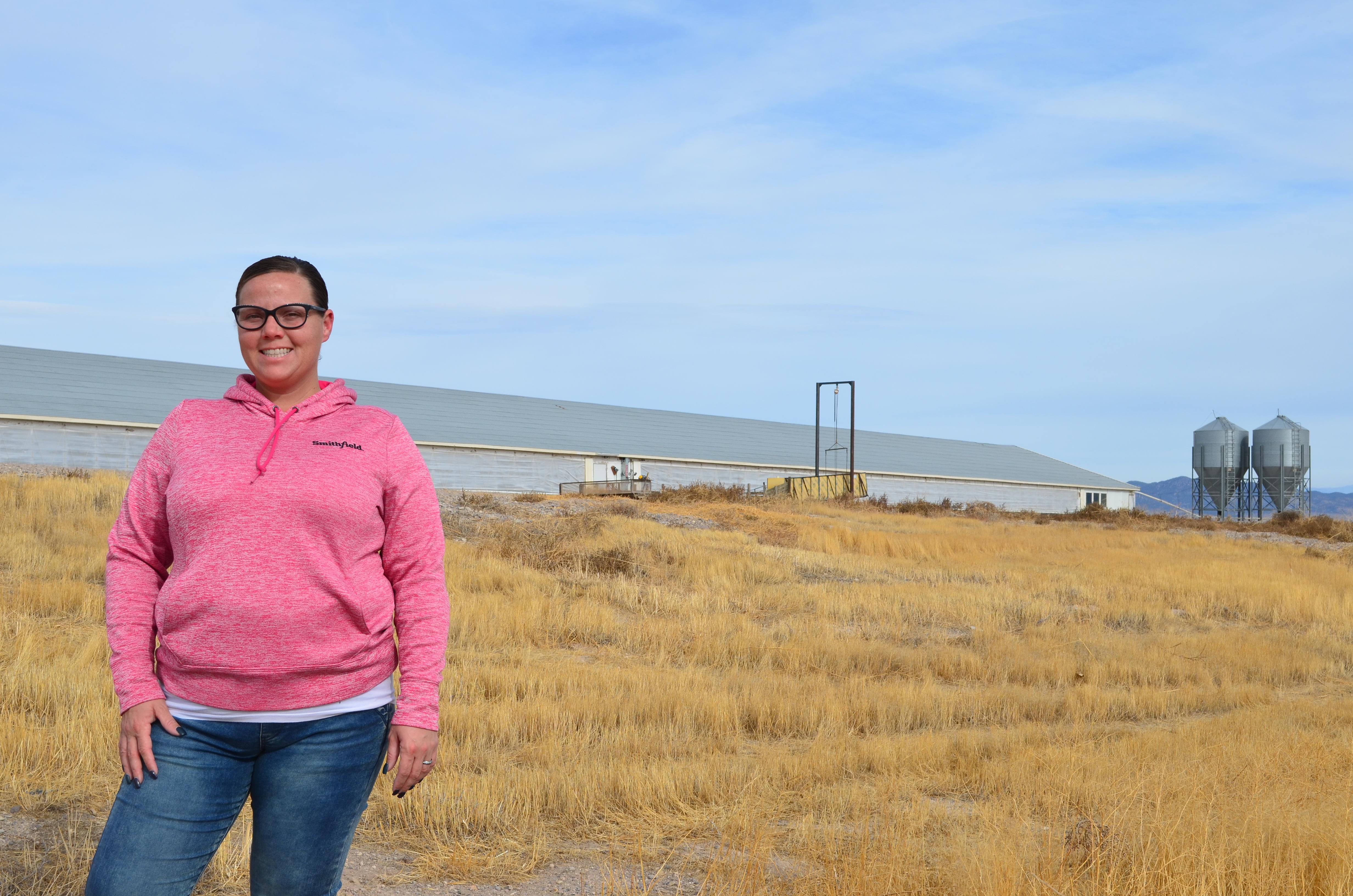 female pig farmer, standing outside of a barn